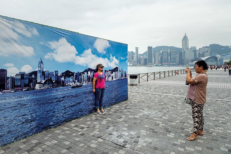 Girl taking photo against Hong Kong city skyline backdrop