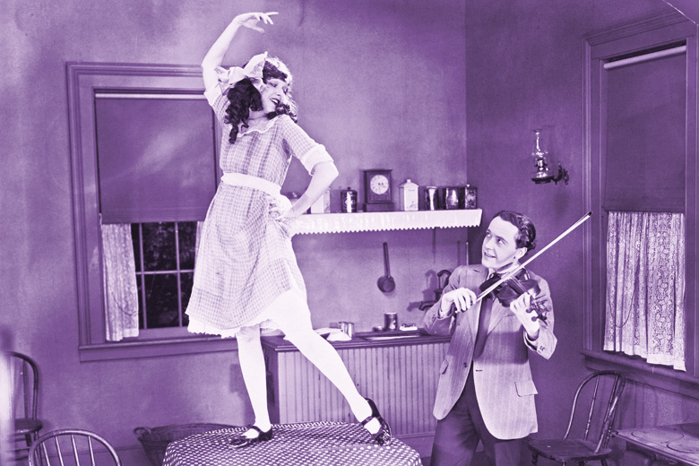Husband playing violin while wife dances on table