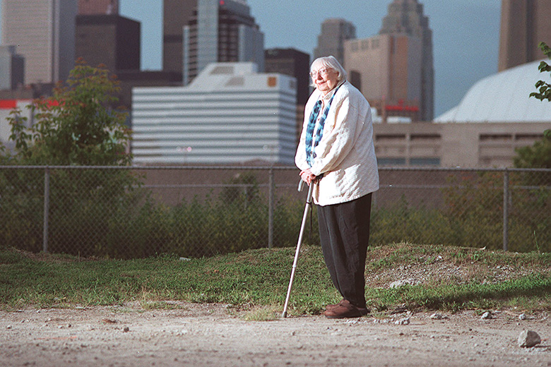 Jane Jacobs walking with city skyline in background