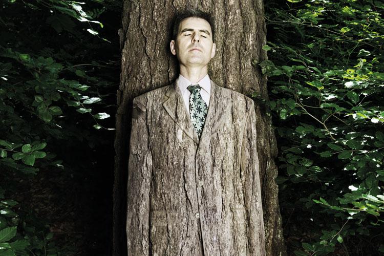 Man camouflaged against tree bark