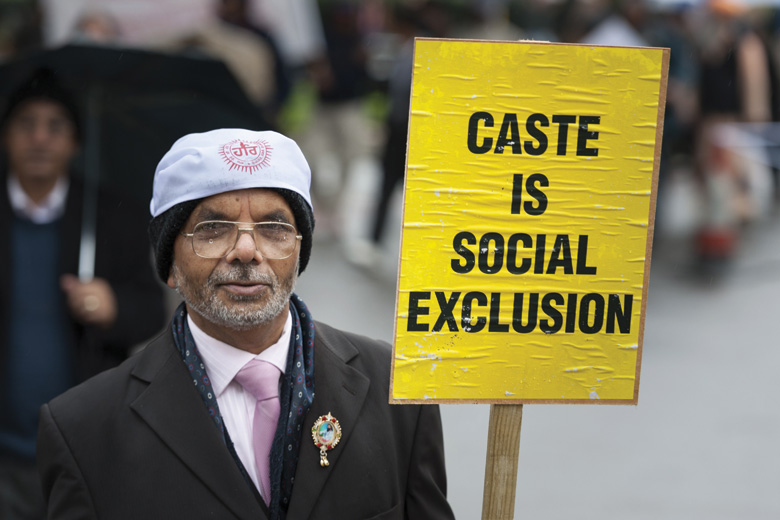 Man holding 'Caste is social exclusion' sign