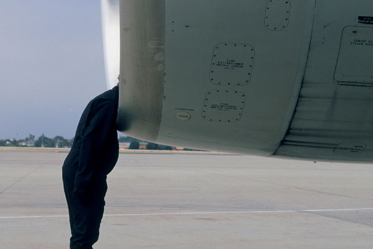 Man leaning head into jet engine