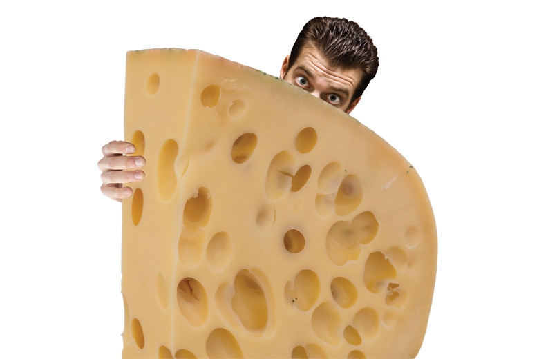 Man peeking from behind piece of swiss cheese