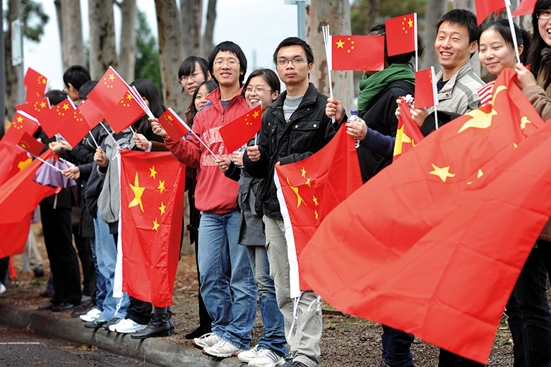Chinese consular staff wave national flags in front of a demonstration by supporters of the Falun Gong spiritual movement outside the venue where Xi Jinping opened Australia's first Chinese Medicine Confucius Institute, in 2010.