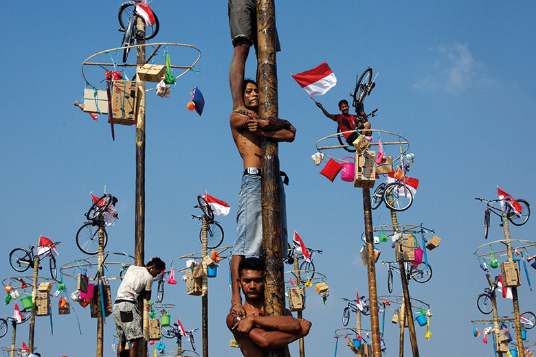 Men climb poles during Panjat-Pinang in Indonesia