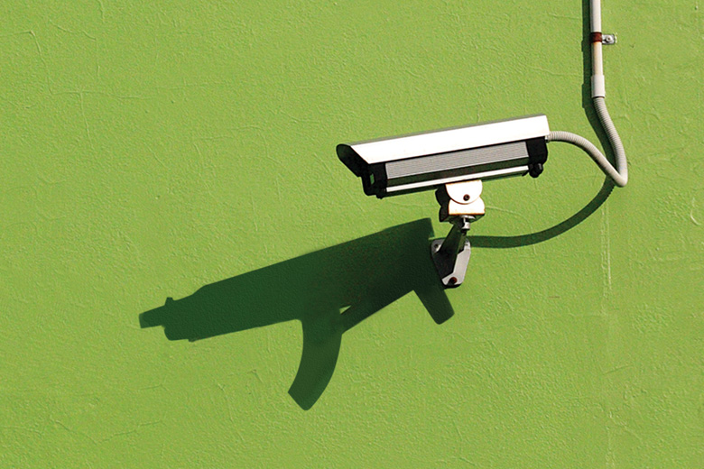 Mounted CCTV camera casting shadow of automatic weapon