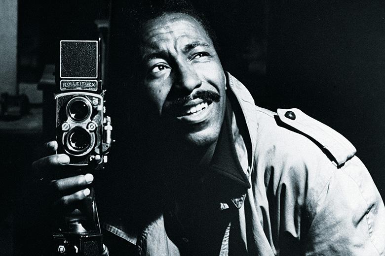 Photographer Gordon Parks posing with camera