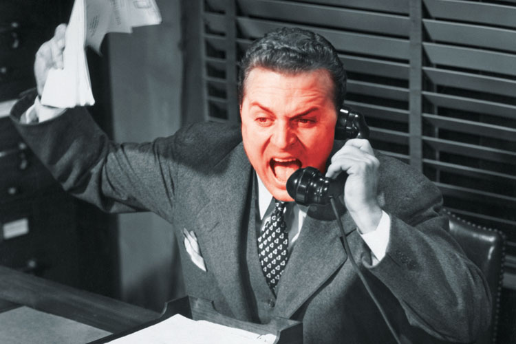Red-faced businessman shouting into telephone
