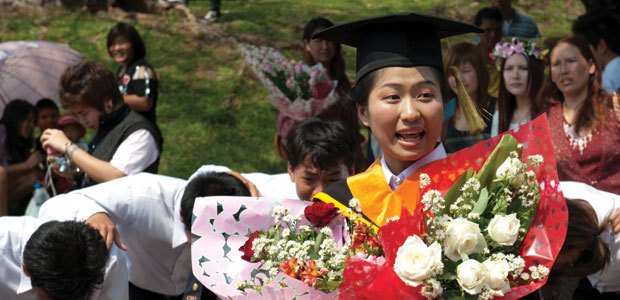 Thai female graduate holding bunches of flowers