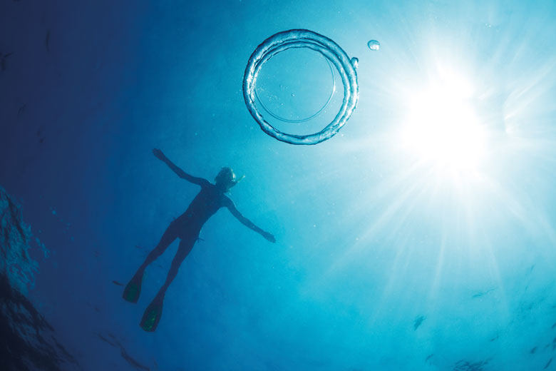 Scuba diver swimming in clear blue water