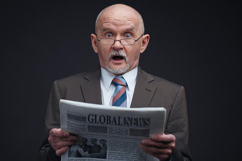 Shocked man reading newspaper