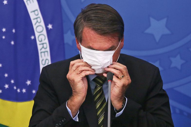 President of Brazil Jair Bolsonaro adjusts his protective mask during a press conference in March 2020