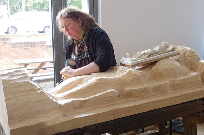 Carving a wooden figure of a corpse