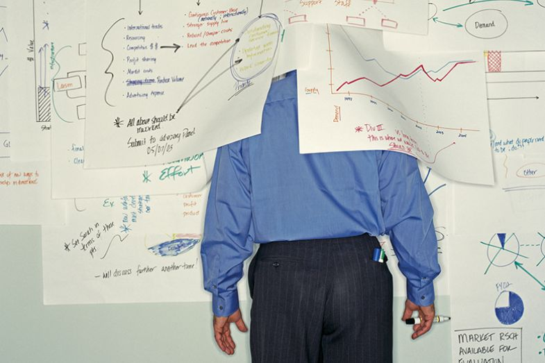 Man partially covered with charts