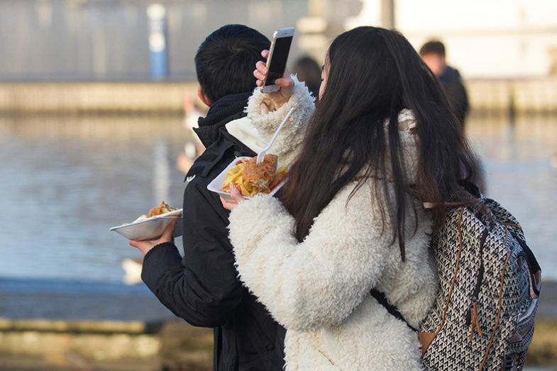 woman eating chips and taking a photo