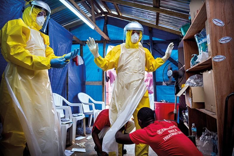 Western aid workers are helped into their PPE by two local staff at an ebola treatment centre in Sierra Leone