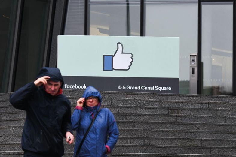 People pass in front of European HQ of Facebook