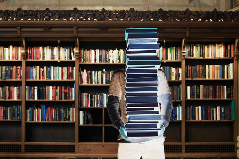 figure holding stack of books
