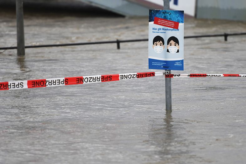 A sign for the compulsory wearing of face masks during the coronavirus pandemic is seen on the banks of the flooded Rhine river in Koenigswinter, western Germany, on February 3, 2021
