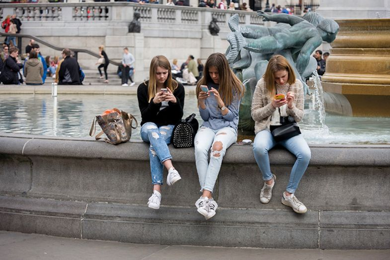 Three young women sit on fountain in Trafalgar Square looking at phones