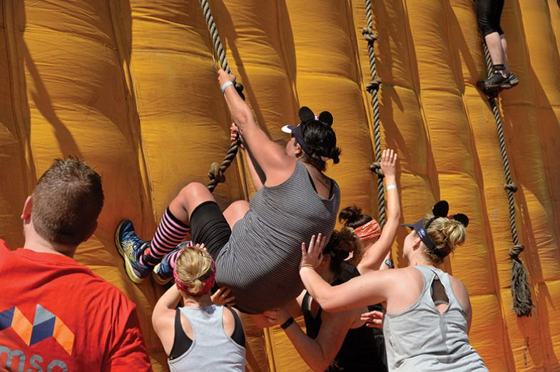 Contestants climb an inflatable wall during the Strongman obstacle race in 2019, in Paarl, near Cape Town. Symbolising helping up black postgrads