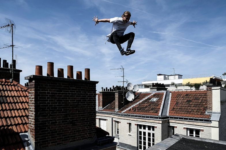Man jumping above houses