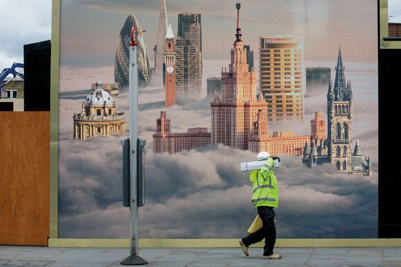 man walking past buildings