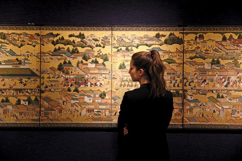 Woman looking at historic Asian painting