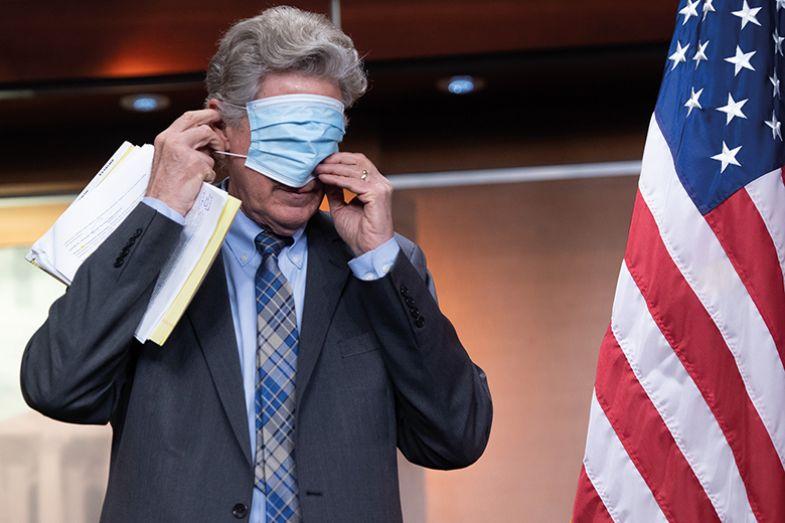 man puts on mask beside US flag