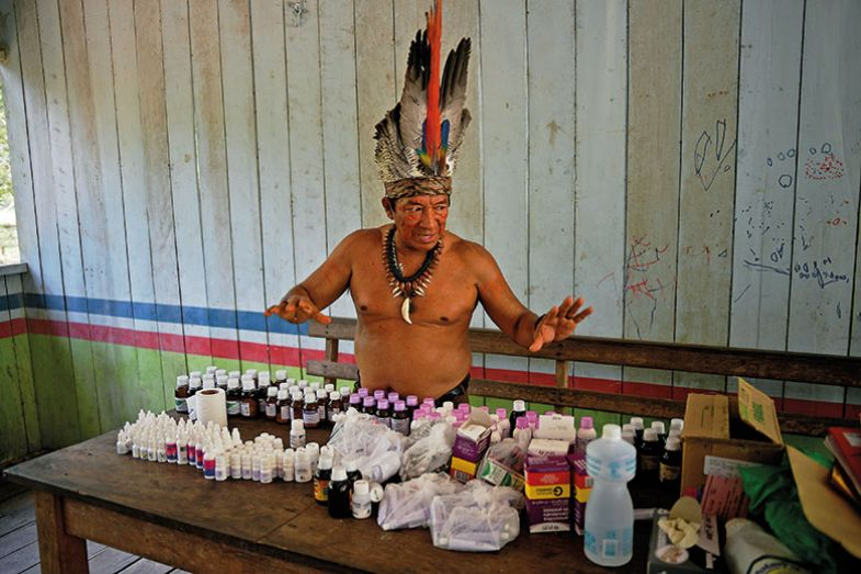 Chief Marcelino Apurina, of the Aldeia Novo Paraiso in the Western Amazon region of Brazil near Labrea, stands by a table of modern medicines delivered to the village on September 21, 2017