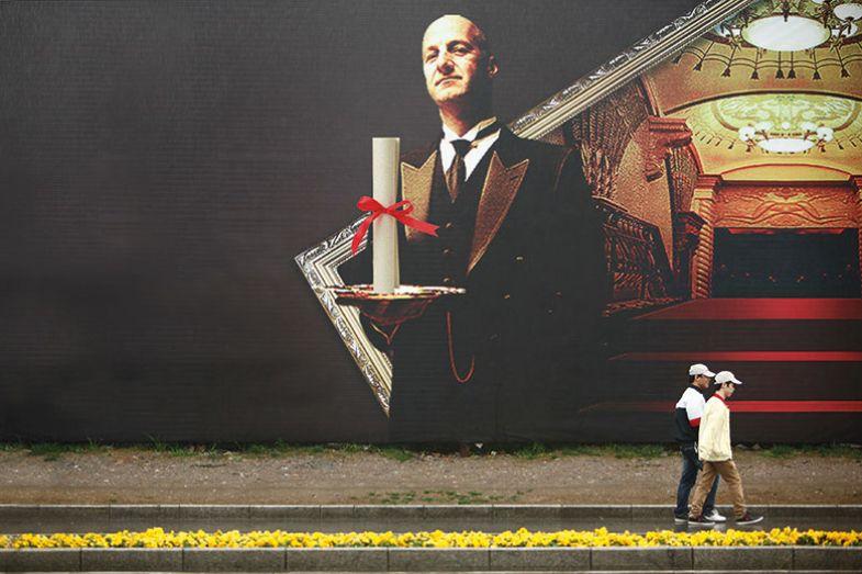 men walk past diploma