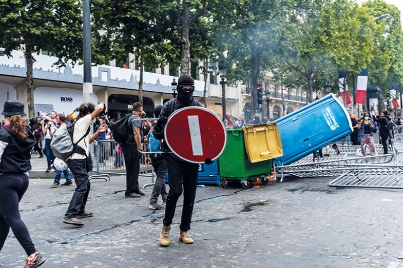 A demonstrator holds a STOP sign as a shield during gilets jaunes protests on the Champs-Elysees