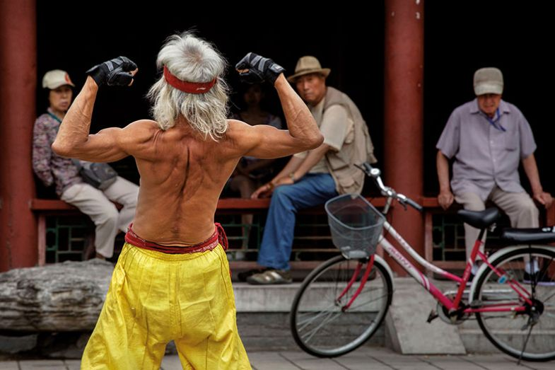 elderly Chinese man flexes his muscles as he performs a martial arts routine on the street, Beijing, China