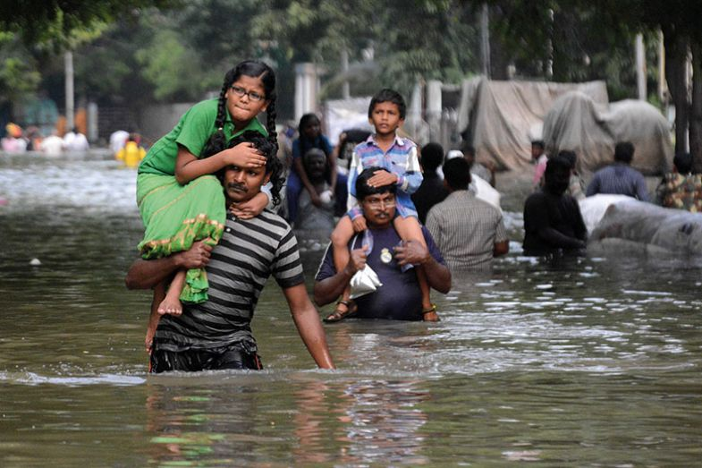 Indian residents carry children as they walk through floodwaters in Chennai on December 3, 2015