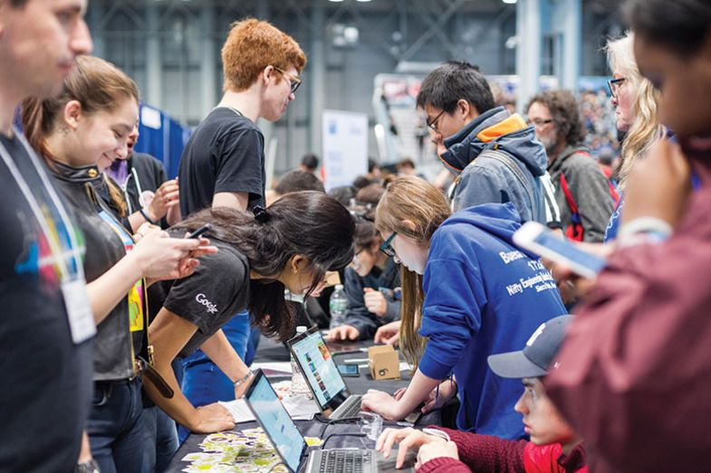 Workers from Google interact with visitors at a Career Expo