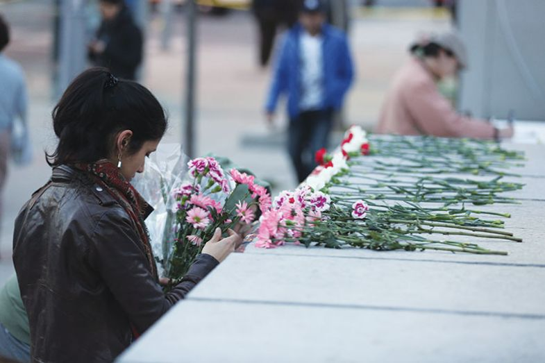 Victims of brutal violence: a woman lays flowers at a memorial set up after incel Alek Minassian drove a van into pedestrians in Toronto in 2018, killing 10 and injuring 16