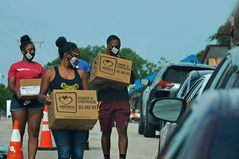 Volunteers deliver food to cars at a Covid-19 testing site at Paul Quinn College in Dallas, Texas on 29 July 2020