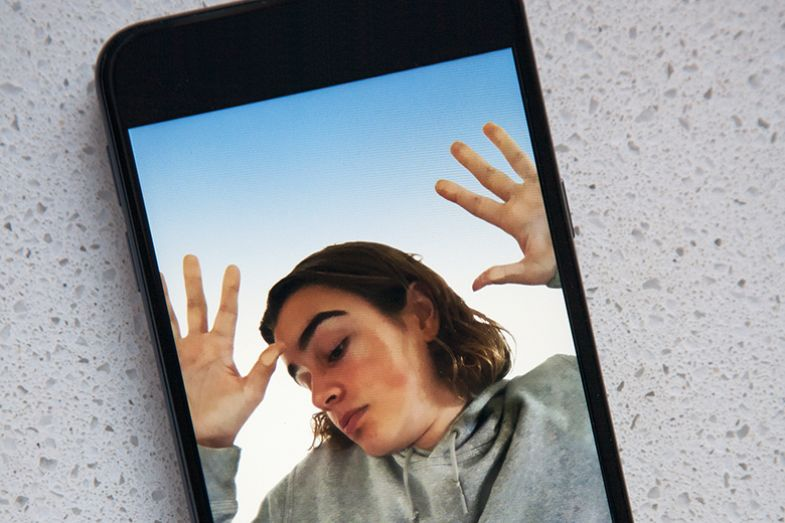 Young woman trapped in a mobile phone