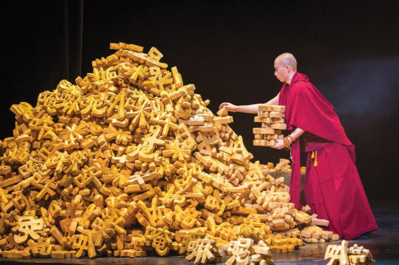 A Buddhist monk stacks models of Chinese characters from a large pile