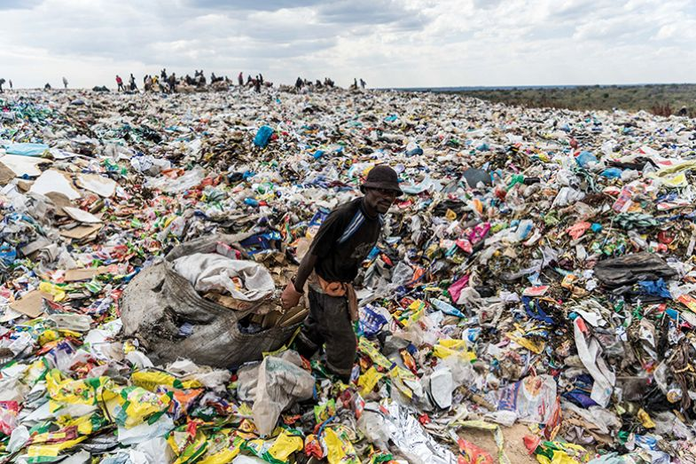 A recycler drags a bag of paper past a heap of non-recyclable material at a sanitary landfill site in Bulawayo, Zimbabwe