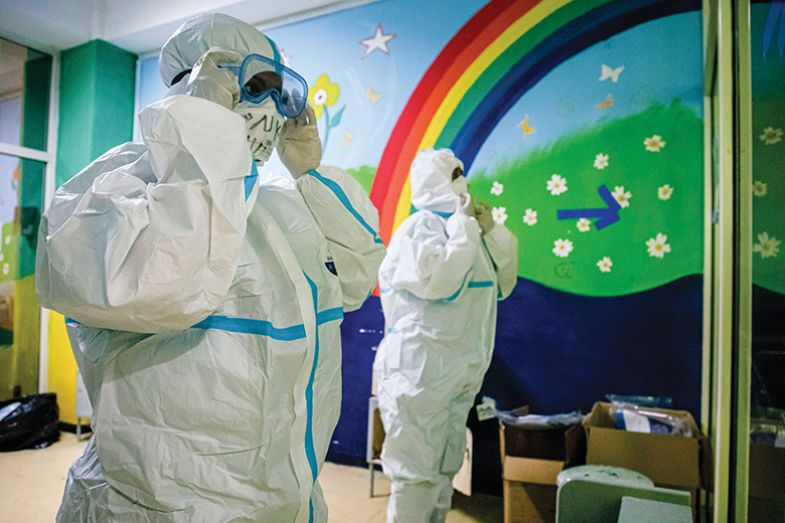 People in PPE in front of a rainbow mural