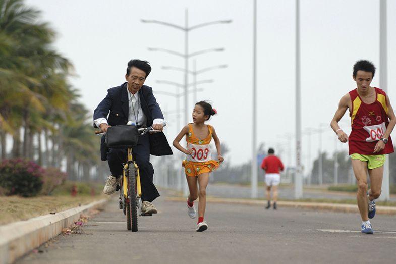 girl runs beside man on bike