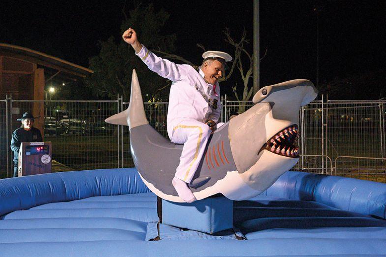 Man in sailor uniform riding mechanical shark