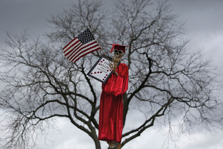 Skeleton in an academic gown holding a flag and placard