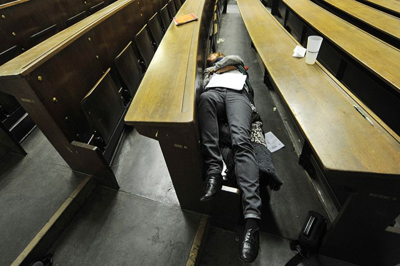 Student asleep in a lecture hall illustrating analysis of status of postdoctoral researchers