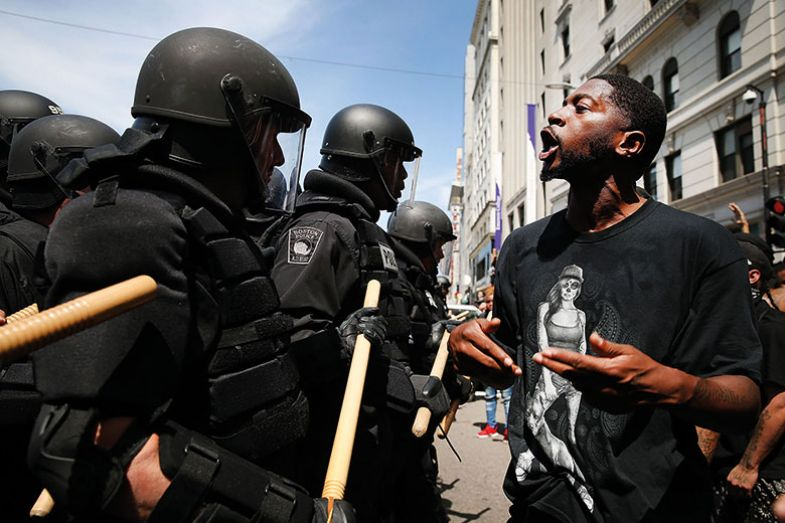 Man in front of riot police during rally in solidarity with Charlottesville, US