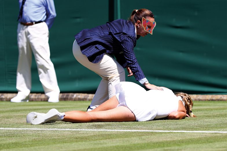 Tennis player lying face-down on the court