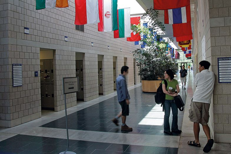 Students standing underneath flags in corridor