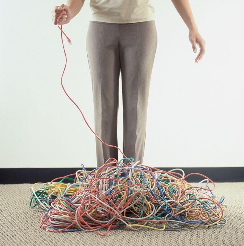 Woman holding a wire coming from a pile of wires on the floor