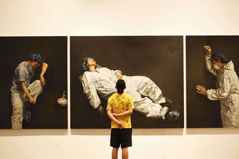 Visitor looks at art exhibition on coronavirus prevention and control at Sichuan Fine Arts Institute in Chognqing, China